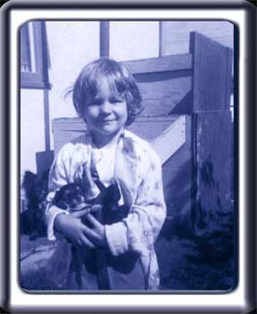 A four year old Mikella holds a puppy in a run down back yard.
