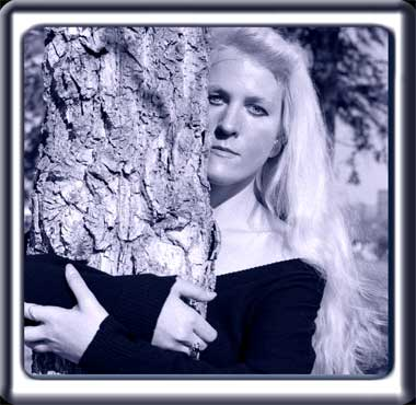 A young woman with long blonde hair stands beside a tree.